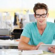 Man Using Digital Tablet In Busy Creative Office — Stock Photo #25045947