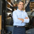 Portrait Of Man With Fork Lift Truck In Warehouse - Stock Photo