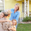 Family Welcoming Husband Home On Army Leave - Stock Photo