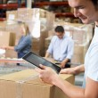Worker Using Tablet Computer In Distribution Warehouse — Stock Photo