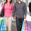 Couple Carrying Shopping Bags On City Street - Lizenzfreies Foto