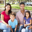 Family Sitting On Park Bench Together - Foto Stock