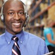 Businessman Using Headset In Distribution Warehouse — Stock Photo