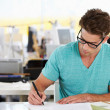 Man Writing At Desk In Busy Creative Office — Stock Photo #25046353