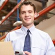 Businessman Scanning Package In Warehouse — Stock Photo #25046433