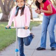 Mother Teaching Daughter To Ride Scooter — Stock Photo