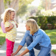 Mother Helping Daughter Tie Shoe Laces On Walk To School — Stock Photo #25046711