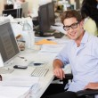 Stock Photo: Man Working At Desk In Busy Creative Office