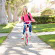 Girl Wearing Rucksack Cycling To School - Stock Photo