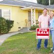 Couple Standing By For Sale Sign Outside Home - Stock Photo
