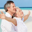 Senior Couple Withs Arms Outstretched On Beautiful Beach — Stock Photo
