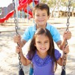 Boy And Girl Playing On Swing In Park — Foto Stock