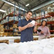 Factory Worker And Manager Checking Goods On Production Line - Stock Photo