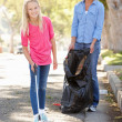 Mother And Daughter Picking Up Litter In Suburban Street - Stock Photo