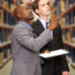 Royalty-Free Stock Photo: Two Businessmen Having Discussion In Warehouse