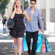 Foto Stock: Fed Up MCarrying Partners Shopping Bags On City Street