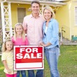 Family Standing By For Sale Sign Outside Home — Stock Photo #25047483