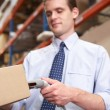Businessman Scanning Package In Warehouse — Stock Photo #25047487