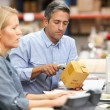 Business Colleagues Working At Desk In Warehouse — Stock fotografie