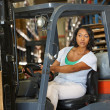 Stock Photo: Woman Driving Fork Lift Truck In Warehouse