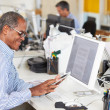 Man Using Digital Tablet In Busy Creative Office — Foto de Stock