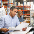 Business Colleagues Working At Desk In Warehouse — Stock Photo #25048073