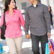 Couple Carrying Shopping Bags On City Street - Stock Photo