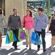 Group Of Friends Carrying Shopping Bags On City Street — Stock Photo