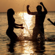 Foto Stock: Silhouette Of Family Having Fun In Sea On Beach Holiday