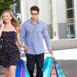 Stockfoto: Fed Up MCarrying Partners Shopping Bags On City Street