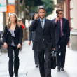 Stock Photo: Group Of Businesspeople Walking Along Street
