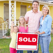 Family Standing By Sold Sign Outside Home — Stock Photo #25048313