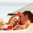 Romantic Couple Relaxing In Beach Hammock - Foto Stock