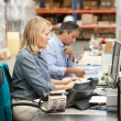 Business Colleagues Working At Desk In Warehouse — Stock Photo #25048421