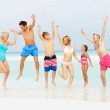 Multi Generation Family Having Fun In Sea On Beach Holiday — Stock Photo #25048457