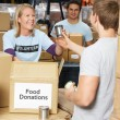 Volunteers Collecting Food Donations In Warehouse — Stock Photo #25048695