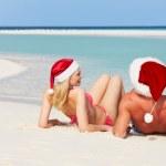 Couple Sitting On Beach Wearing Santa Hats — Stock Photo