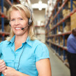 Businesswoman Using Headset In Distribution Warehouse — Stock Photo