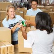 Volunteers Collecting Food Donations In Warehouse - Foto Stock