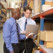 Two Businessmen With Laptop In Warehouse — Stock Photo #25048839