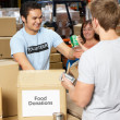 Volunteers Collecting Food Donations In Warehouse — Stock Photo #25048869