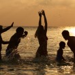 Foto Stock: Silhouette Of Multi Generation Family Having Fun In Sea