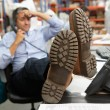 Businessman Putting Feet Up On Desk In Warehouse — Stock Photo #25049333