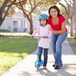 Mother Teaching Daughter To Ride Scooter - Stock Photo