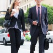 Businessman And Businesswoman In Street With Takeaway Coffee - Stock Photo