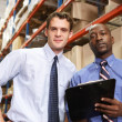 Two Businessmen With Clipboard In Warehouse — Stock Photo #25049475