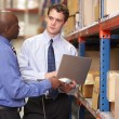 Stock Photo: Two Businessmen With Laptop In Warehouse