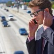 Businessman Speaking On Mobile Phone By Noisy Freeway — Stock Photo