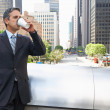 Royalty-Free Stock Photo: Businessman Drinking Takeaway Coffee Outside Office