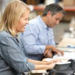Business Colleagues Working At Desk In Warehouse — Stock Photo #25049673